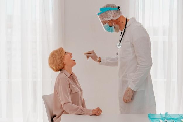医者はテスターでcovidウイルスをチェックしています