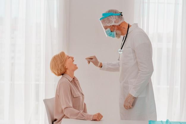 의사가 테스터로 코비드 바이러스를 확인하고 있다