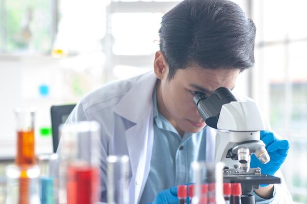 医者は顕微鏡をやっています研究のために、風邪の治療としてのワクチン