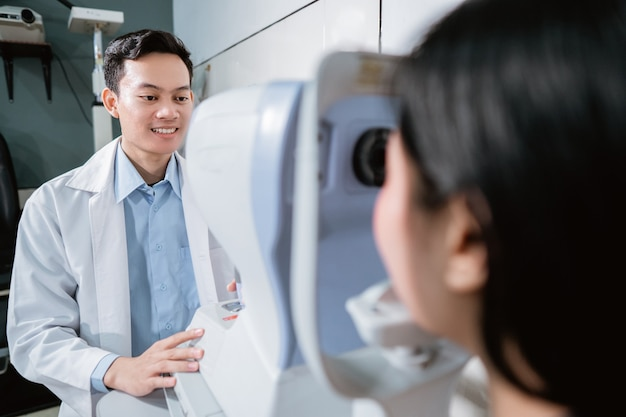 A doctor is examining a female patient using an eye computer at an eye clinic
