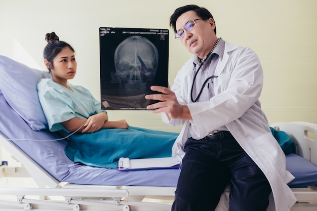Doctor is explaining about the brain x-ray results to a female patient lying in bed at a