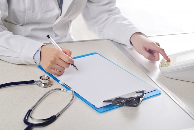 The doctor is filling in the medical record.