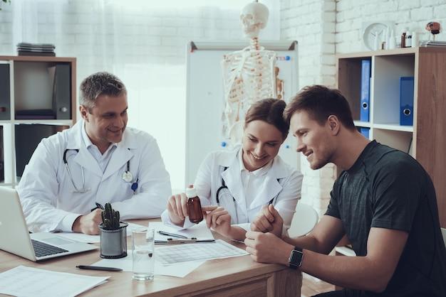 의사는 병원에서 운동 선수에게 병을주고있다.