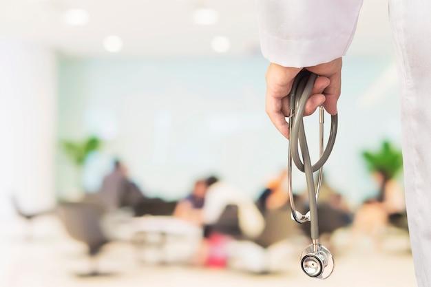 의사는 앉아있는 사람들을 통해 자신의 청진기를 사용하여 환자를 검사하려고합니다