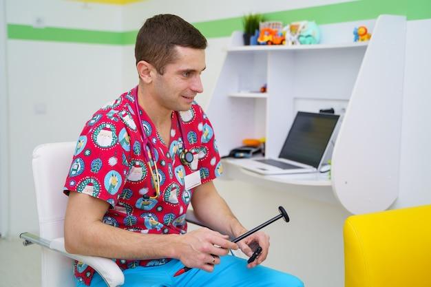 의사는 블랙 험머로 반사를 테스트할 것입니다. 소아과 개념입니다. 밝은 수술복을 입은 의사.