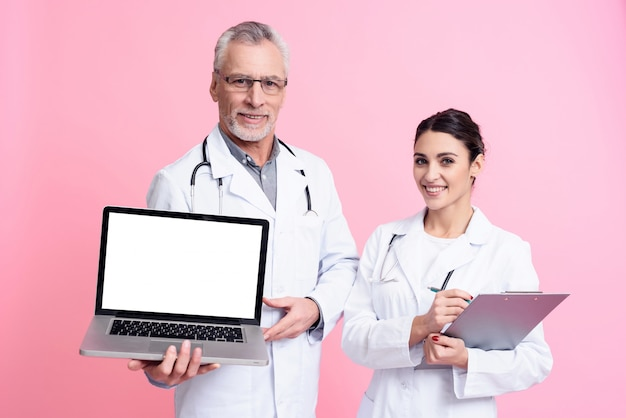 Doctor is holding a laptop and a girl is holding a notepad