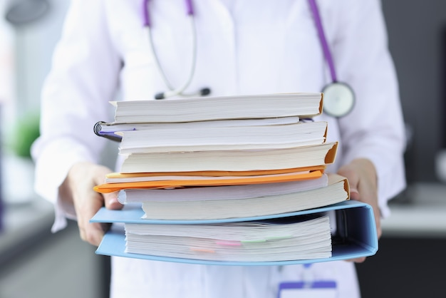 Doctor is holding large stack of folders. disease history concept