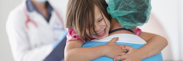 医者はおびえた少女を腕に抱いています