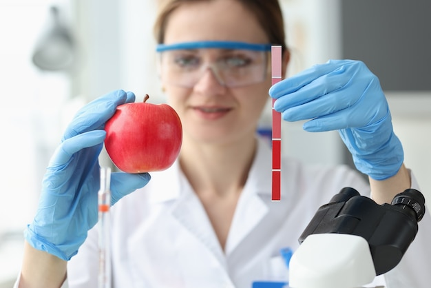 Doctor is holding red apple and strip with measurements determination of ripeness of fruit