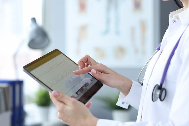 Доктор держит таблетку с кардиограммой сердца. изучение концепции сердечно-сосудистой системы