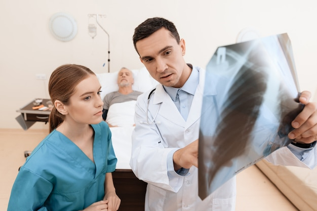 Doctor is holding an x-ray, nurse is standing next to him.