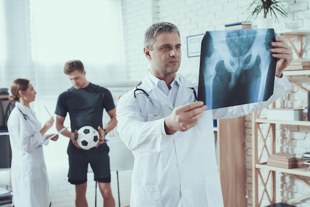 Doctor is looking at x-ray for athlete