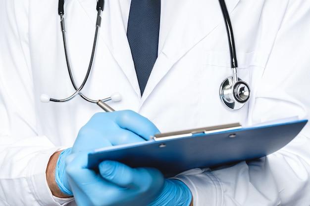 医師がレポートまたは病歴にメモを取っている