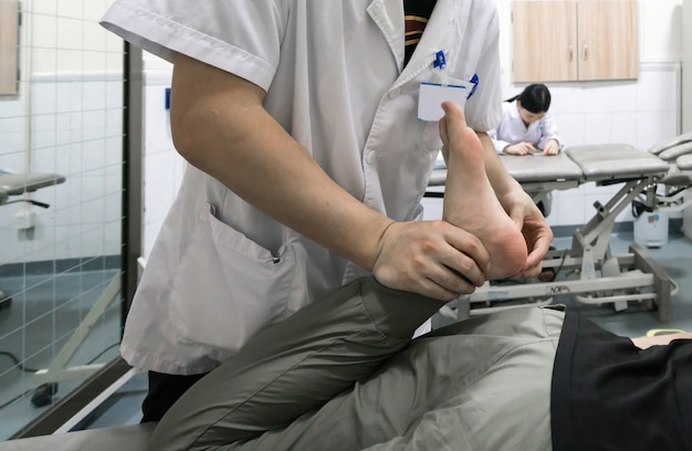 The doctor is rehabilitating the patient's legs