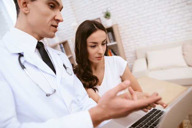Doctor is showing something on laptop to a pregnant girl.
