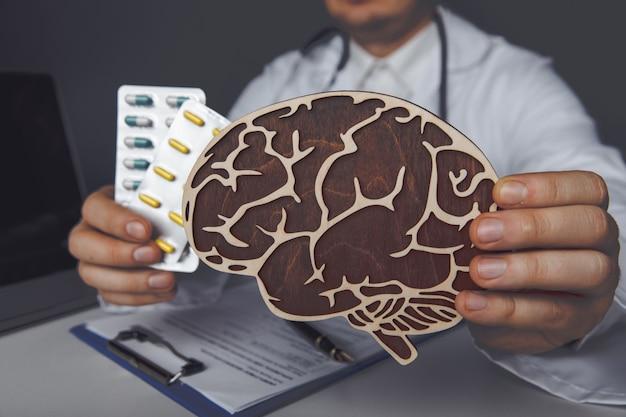 Доктор показывает деревянный мозг и таблетки. концепция здравоохранения и лечения.