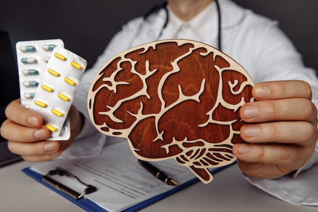 Doctor is showing wooden brain and pills importance of early diagnosis and treatment concept