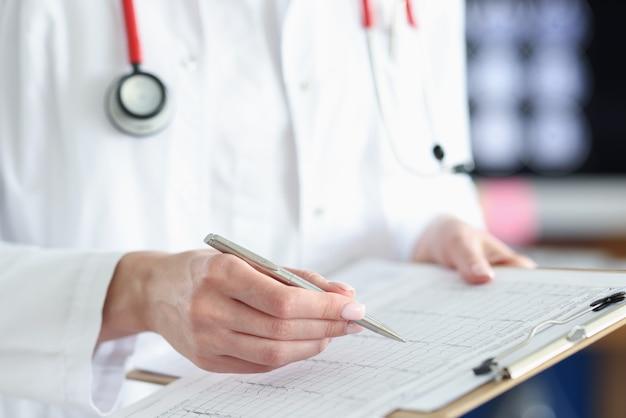의사는 환자 심장의 심전도 해독을 연구하고 있습니다.