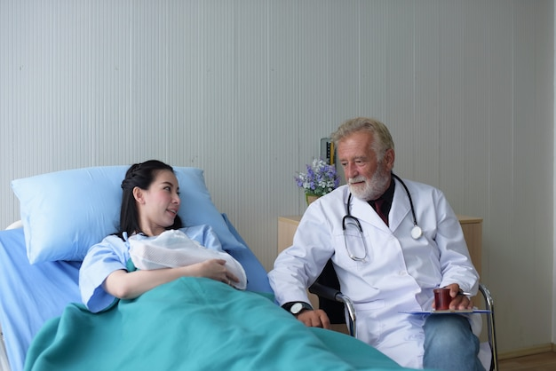 The doctor is taking care of the patient and checking the body and talking to the patient at the hospital.