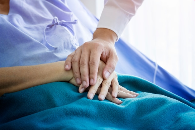 Doctor is taking care with old female patient in the hospital
