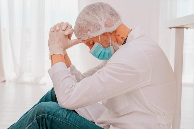 의사는 코비드 바이러스 전염병으로 인해 피곤하고 스트레스를 받습니다.