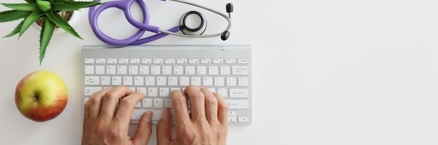Врач печатает на клавиатуре рядом со стетоскопом и яблоком