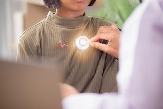 Врач использует стетоскоп для обследования пациента. чтобы услышать частоту сердечных сокращений, для пациентов с сердечными заболеваниями.