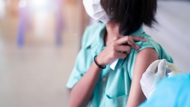 의사가 코로나바이러스 또는 covid-19를 예방하기 위해 제복을 입은 학생들에게 예방접종을 하고 있습니다