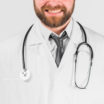 Doctor in lab coat and stethoscope smiling