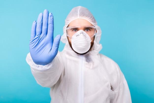 Doctor or lab scientist wearing biohazard protective suit hand gesturing stop coronavirus covid-19