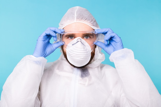 Doctor or lab scientist wearing biohazard protective suit puts on safety glasses, close-up of face