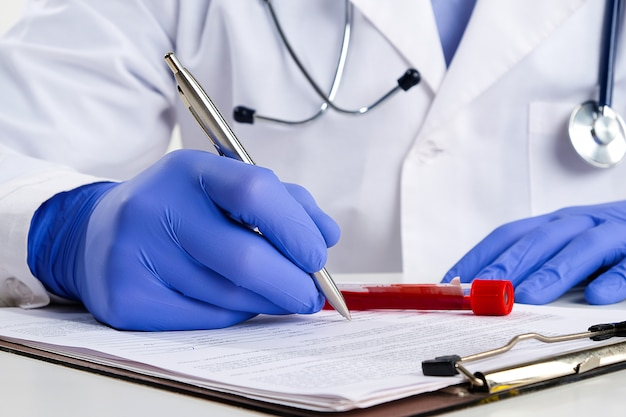 A doctor or laboratory assistant fills out medical forms. next to it is a test tube with blood for testing.
