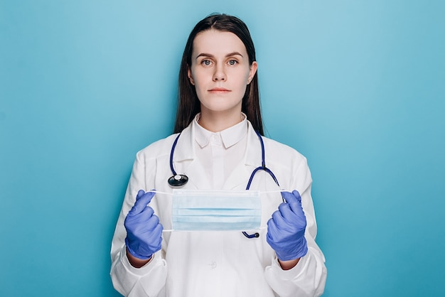 Doctor in latex gloves holding medical protective face mask