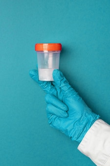 Doctor in latex gloves holds a plastic container with semen or saliva samples on a blue background. medical concept.