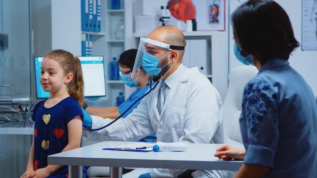 의사는 의료용 장갑을 끼고 청진기를 들고 아이의 호흡을 듣고 있습니다. covid-19 동안 병원에서 의료 서비스, 상담, 치료를 제공하는 마스크를 쓴 소아과 전문의