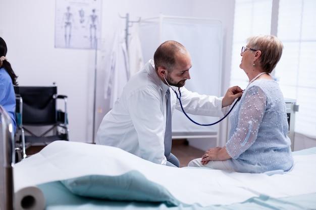 彼女が検査のために病院のベッドに座っている間、年配の女性の心拍を聞いている医者