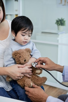 Doctor listening to heart of of teddy bear in hands of little kid to calm him before examination