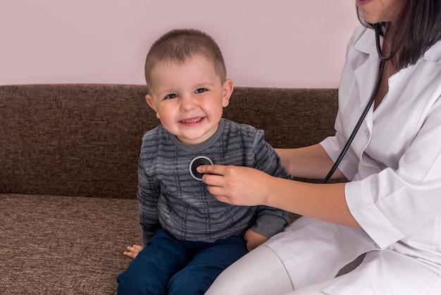 聴診器を通して小さな男の子の呼吸を聞いている医者