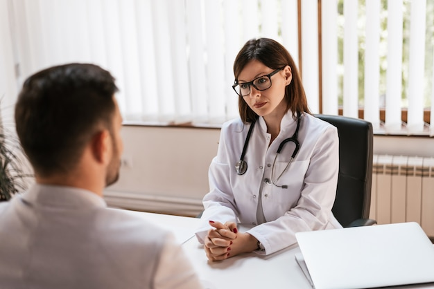 Doctor listening to a patient at her office