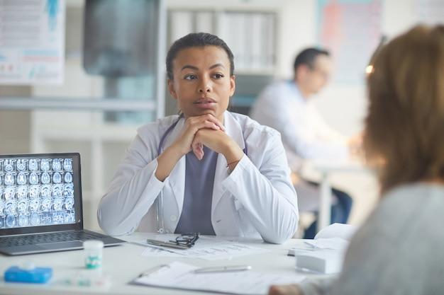 Доктор слушает ее пациента в офисе