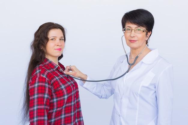흰색 배경 위에 청진 기로 환자의 가슴을 듣고 의사.