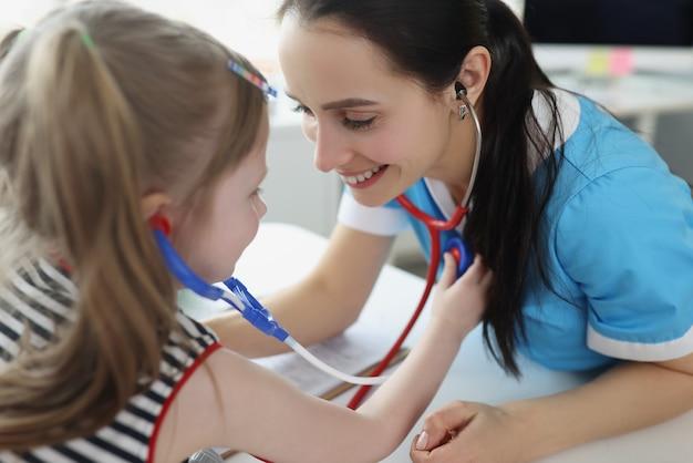 聴診器で小さな女の子に耳を傾け、クリニックで彼女と遊んでいる医師
