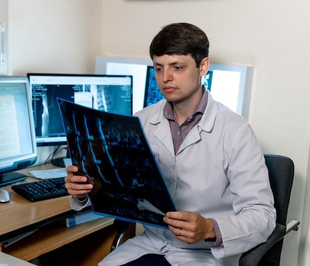 コンピューターの近くのx線画像を見て医者。磁気共鳴画像装置の診断。職場のスペシャリスト。