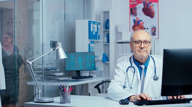 Врач смотрит в камеру после набора текста на компьютере в современной частной клинике, работает в комнате для консультаций, в то время как медсестра в спине разговаривает с пациентом. стеклянные стены