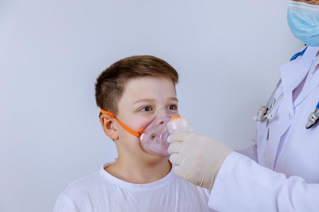 酸素マスクを通して吸入している子供の患者を見ている医者