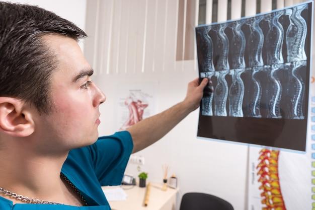 Доктор, глядя на рентгеновское изображение, показывающее позвоночник