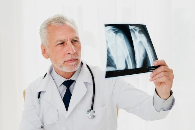 Доктор смотря рентгеновский снимок