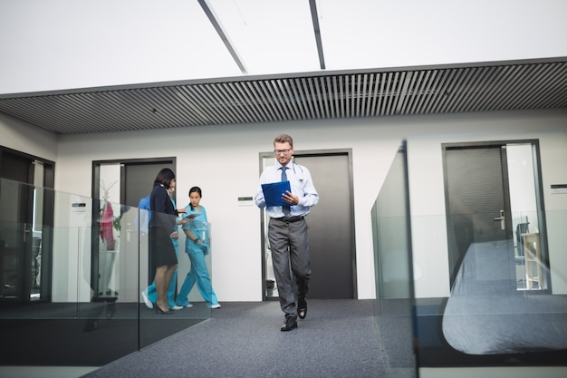 Doctor looking at medical report while walking