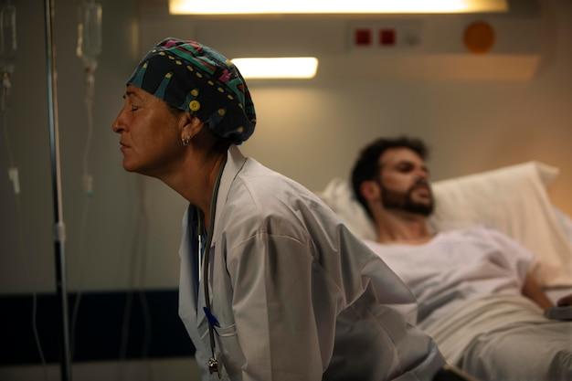 Dottore che sembra triste accanto a un paziente