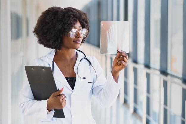 医者は病院で肩のx線フィルムを探しています。 x線撮影のコンセプトです。病室で患者のx線フィルムを調べる放射線医学女医。
